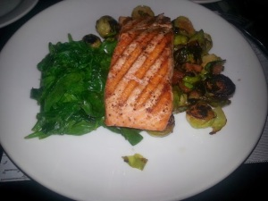 Wood-grilled salmon, sauteed spinach, and bacon braised brussel sprouts